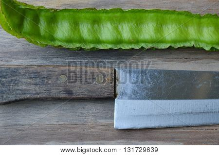 wing bean and kitchen knife handle on wooden board