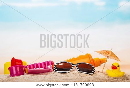 Children's toys, sunglasses and cream in the sand against the sea.
