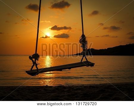 Silhouette of rope swing hang over beach at sunset.
