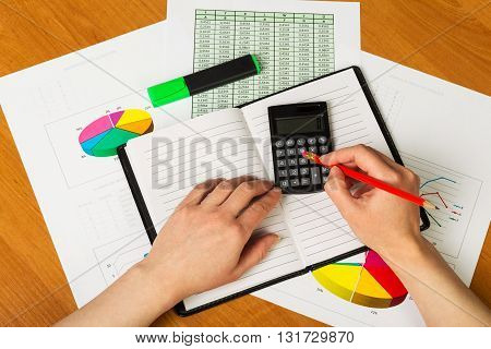 Human hand with pencil and calculator finds a notebook, a marker on the desktop.