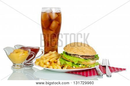 Hamburger, french fries, sauces, glass of cola and cutlery isolated on white background.