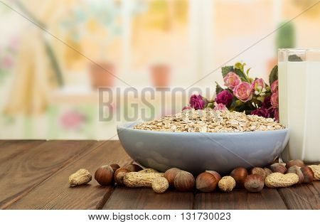 Healthy diet for adults: a bowl of oatmeal, a glass of milk and nuts on the background of the kitchen.
