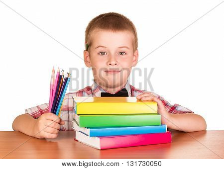 Cute student with books and crayons at the table on a white background.