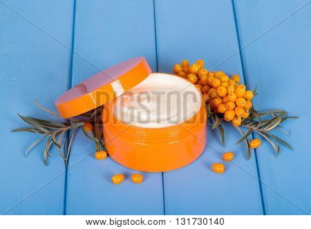 Jar of cream with essential oils of sea buckthorn on a tree colored in blue background.