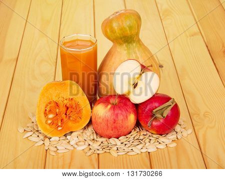 A glass of pumpkin juice, apples and seeds on a background of light wood.