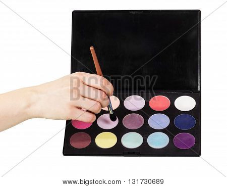 Palette of colorful eye shadows and cosmetic brush in a female hand isolated on white background.