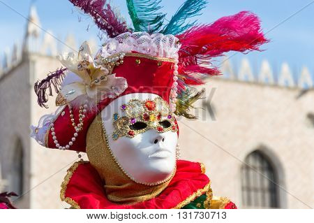 Venice, Italy - February 15, 2015: Portrait of an unidentified person on a colorful carnival costume, posing in front of the Doges Palace during the Carnival of Venice, in Italy.