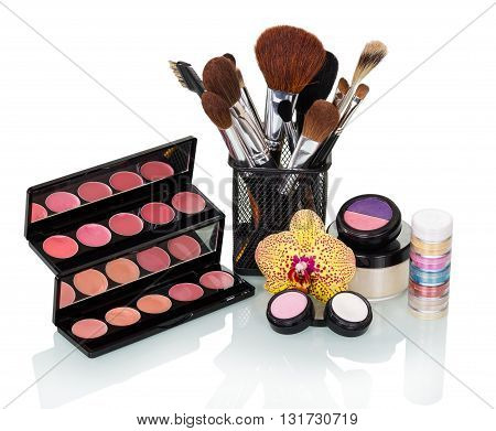 Cosmetic brush, eyeshadow, blush, lip gloss and orchid flower isolated on white background.