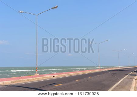 Asphalt road and sea with street light