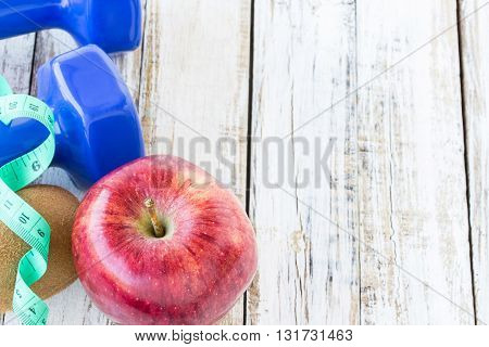 Red apple dumbbelle and measuring tape on white wooden background