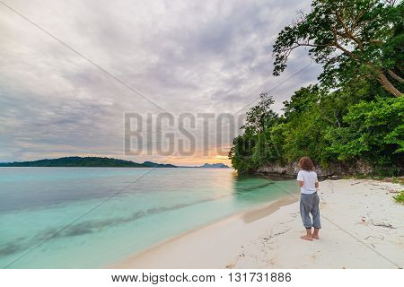 Tourist Watching A Relaxing Sunset Sitting On The Beach In The Remote Togean Islands, Central Sulawe