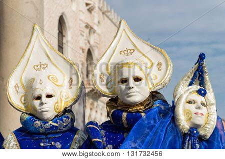 Venice, Italy - February 15, 2015: Two unidentified persons wearing the same costume, in front of the Doges Palace during the Carnival of Venice, in Italy.