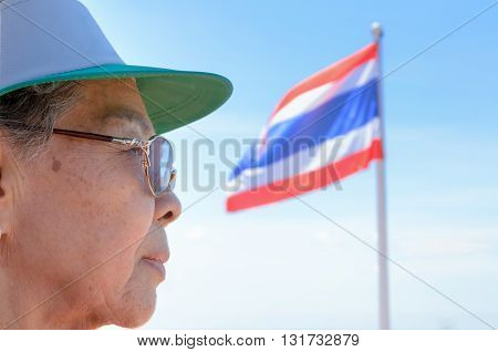 Face side old women Thai people and Thailand flag on a blue sky background