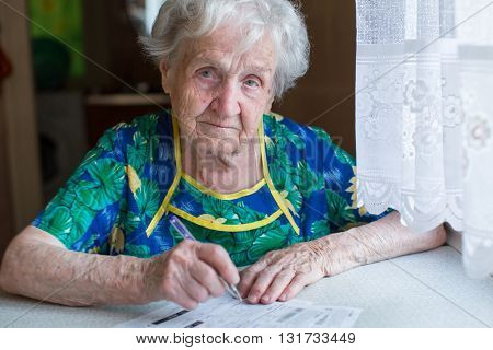 Elderly woman fills in receipts for utilities.