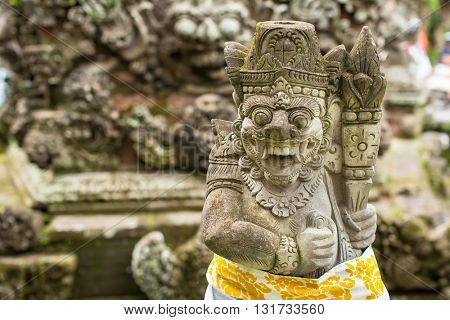 Traditional demon guard statue carved in stone in Bali island, Indonesia.