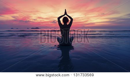 Female yoga silhouette on the beach after sunset.