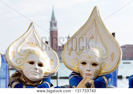 Venice, Italy - February 15, 2015: Two unidentified persons wearing the same costume with San Giorgio Maggiore bell tower in the background during the Carnival of Venice, in Italy.