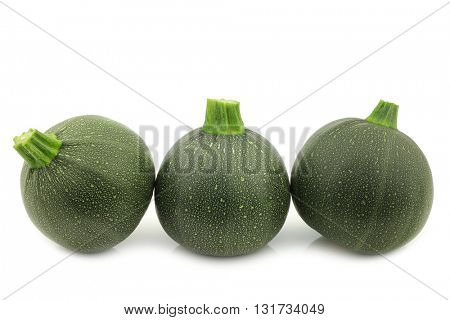 row of fresh round zucchini's on a white background