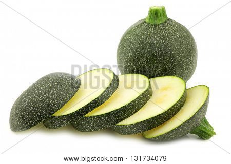 fresh round zucchini and some slices on a white background