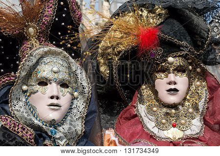 Venice, Italy - February 15, 2015: Two models disguised on colorful carnival costumes during the Carnival of Venice, in Italy.