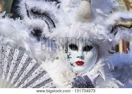 Venice, Italy - February 15, 2015: An unidentified woman in a beautiful white costume, holding a fan and sending kisses at the Carnival of Venice, in Italy.
