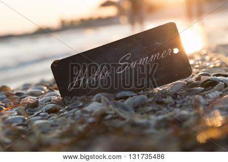Hello Summer inscription on the label, sunset on the beach.