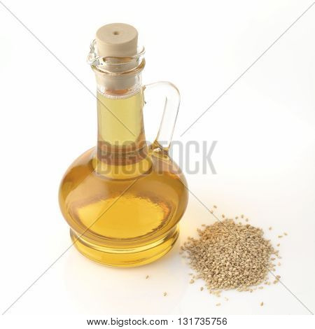 High resolution image of sesame oil decanter with sesame seeds shot in studio on white background