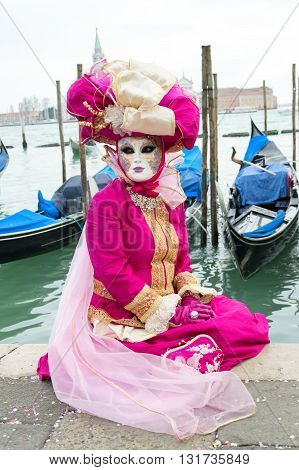 Venice, Italy - February 15, 2015: An unidentified woman on a pink costume posing in front of gondolas during the Carnival of Venice, in Italy.
