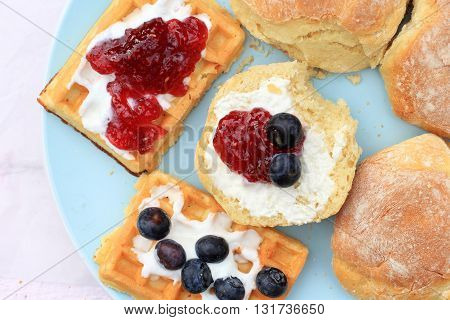 Fresh Scottish scones and belgian waffles with cream and raspberry jam and blueberries