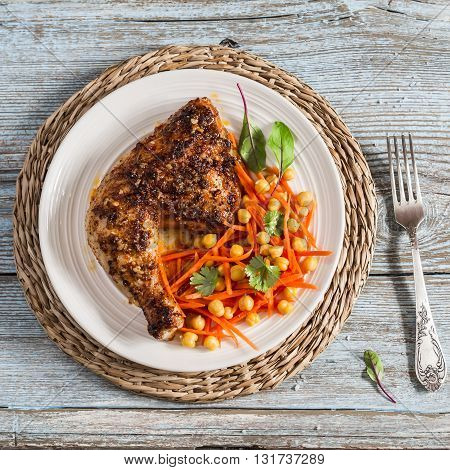 Grilled chicken and fresh carrots chickpea salad on a light wooden background.