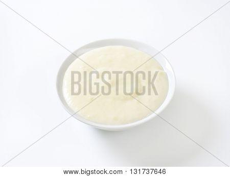 bowl of semolina pudding on white background