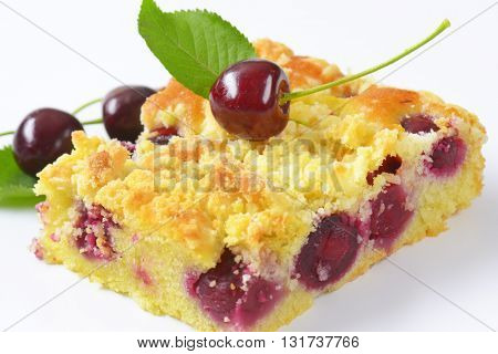 slice of cherry crumb cake on white background - close up