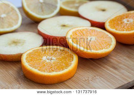 sliced juicy fruits on a wooden board. sliced orange. sliced apple. sliced lemon