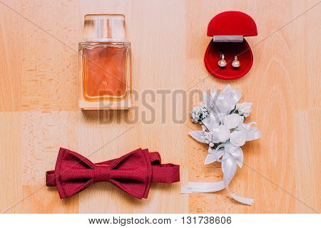 Set of man's and woman's accesories on rustic wooden background. Perfume, burgundy bow-tie, red box with pearl decorated earrings white floral boutonniere.