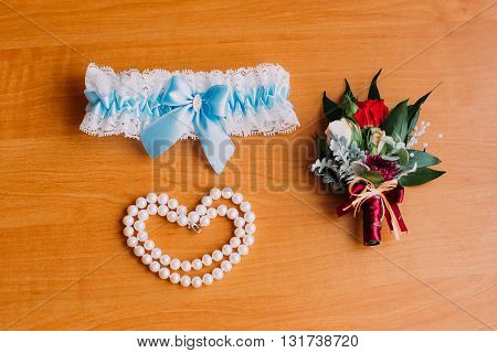 Bride's wedding accessories, white garter with blue ribbon, bracelet of pearls and cute little boutonniere. Preparing for ceremony.
