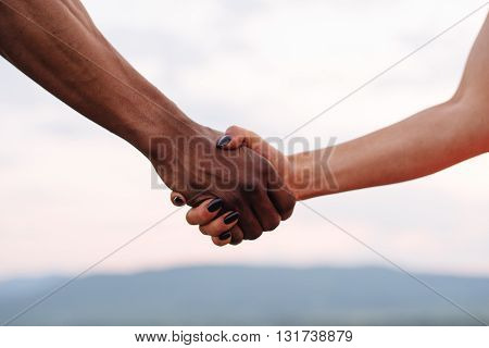 Close-up of mixed race couple holding hands on the misty mountain background. Symbolic photo.