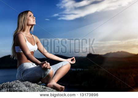 Slender young woman doing yoga exercise outdoors.