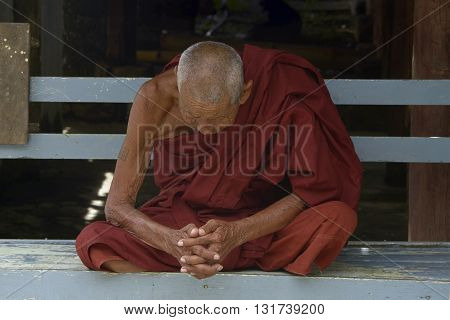 Inle, Burma, september - 10 -2015  very old Buddhist monk makes his meditation sitting on a bench monastery Inle