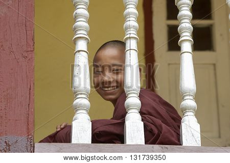 Inle, Burma, september - 10 -2015  Young Buddhist novice smiling at the camera looks through the balcony of the monastery