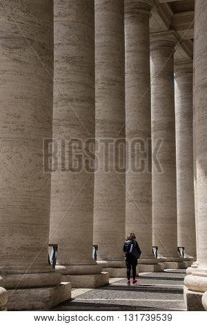 Lady walking through the long stone columns at the side of St Peters Basilica, Rome, Italy, Europe