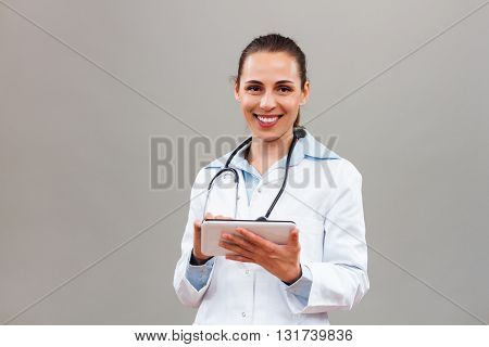 Portrait of beautiful female doctor using digital tablet.