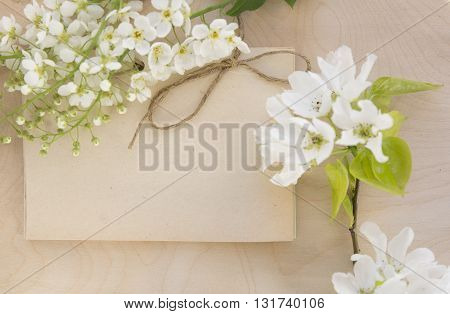 Open vintage handmade sketchbook with white bird-cherry flowers over wooden table background. Mock up retro style. Old paper notepad. Vintage retro mockup. Rough rope. Summer mock-up. Wooden background.