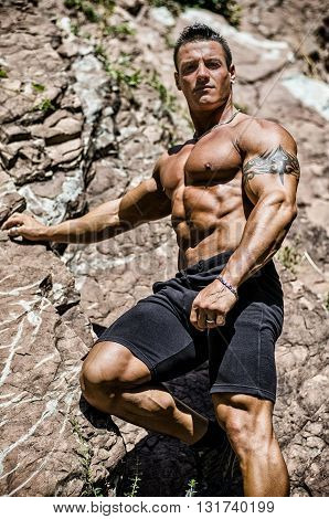 Handsome, muscular, shirless climber, looking in camera and climbing stone wall