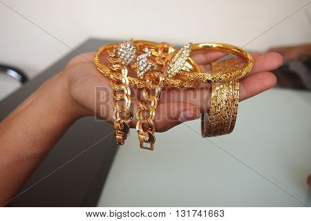 hand side with golden ring and bracelet jewelry