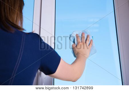 Back View Of Woman Cleaning Window With Rag At Home