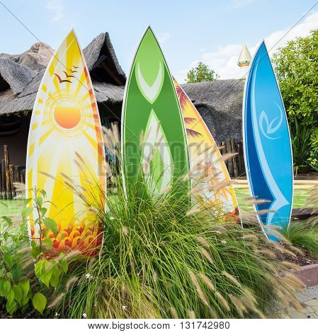 Colorful surfboards in front of a typical Hawaiian hut.