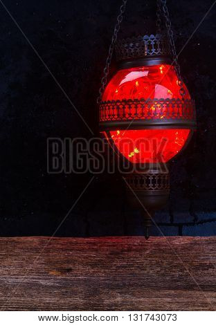 red metal and glass oriental lamp close up glowing in night
