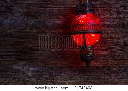 red oriental hanging lamp close up glowing in night