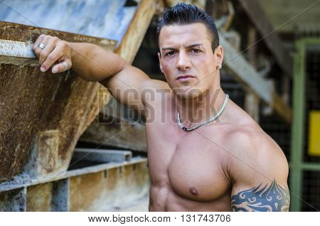Handsome young muscle man shirtless with hand on rusty metal structure, looking at camera