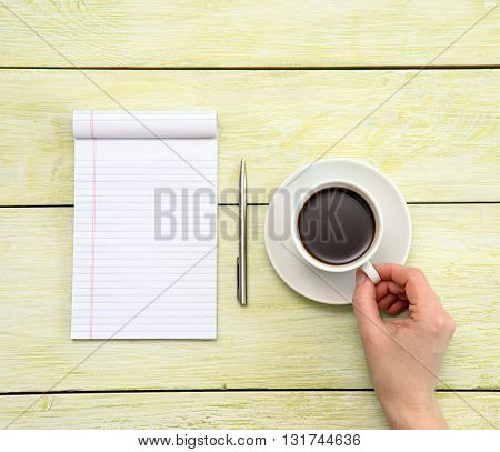 coffee and notebook on wooden background. woman is drink coffe and drawing a something an empty paper